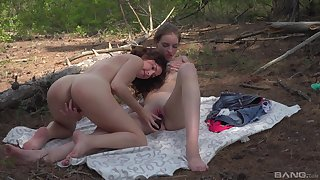 Puberty share a dildo in outdoor scenes in front of the cam